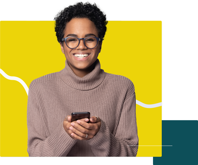 Woman smiling while holding her phone.
