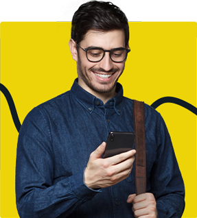 A man smiling while looking at his phone.